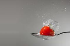 Pomodoro di ciliegia con la spruzzata dell'acqua in un cucchiaio Immagini Stock