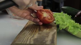 Pomodoro di taglio della donna su un tavolo da cucina affettatura delle verdure su un tagliere di legno video d archivio