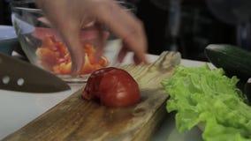 Pomodoro di taglio della donna su un tavolo da cucina affettatura delle verdure su un tagliere di legno stock footage