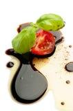 Pomodoro e basilico della fetta sopra aceto balsamico Immagini Stock