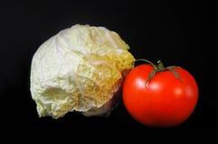 Pomodoro e cavolo su un fondo nero Fotografie Stock Libere da Diritti