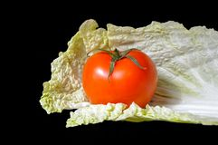 Pomodoro e cavolo su un fondo nero Fotografia Stock