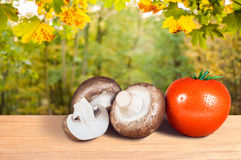 Pomodoro e funghi rossi su una tavola di legno Immagine Stock