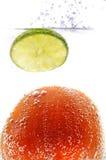 Pomodoro e limone in acqua scintillante Immagine Stock