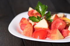 Pomodoro e mele dell'insalata in una ciotola su una tavola scura Immagine Stock Libera da Diritti