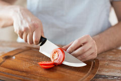 Pomodoro maschio del taglio manuale a bordo con il coltello Fotografia Stock