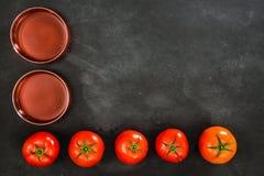 Pomodoro maturo con liquido rosso sulla lavagna Fotografie Stock