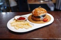 Pomodoro, patate fritte e salsa al pomodoro decorati hamburger in un piatto ovale su una tavola di legno fotografia stock libera da diritti