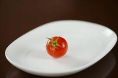Pomodoro rosso con il gambo verde sul piatto ovale bianco Immagini Stock Libere da Diritti