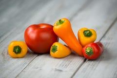 Pomodoro rosso e mini peperoni dolci colorati su un fondo di legno Immagine Stock