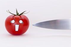 Pomodoro spaventoso del fronte e lama di coltello tagliente Fotografia Stock Libera da Diritti