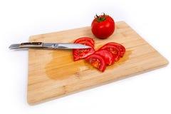 Pomodoro sul bordo di taglio Fotografia Stock