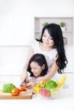 Pomodoro sveglio di taglio della ragazza con la madre fotografie stock