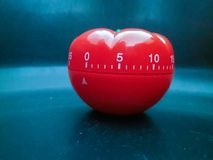 Red pomodoro timer in tomato shape on a black texture background stock image