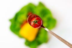 Pomodoro in un cucchiaio su un fondo delle verdure variopinte vaghe immagini stock libere da diritti
