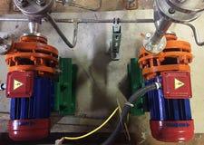 Pomp en motor bij een industriële faciliteit Waarschuw het materiaal in actie Details en close-up stock afbeeldingen