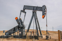 Pompa del pozzo di petrolio in giacimento di petrolio aperto nudo Fotografia Stock Libera da Diritti