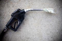 Pompa di gas con soldi nell'ugello Immagini Stock Libere da Diritti