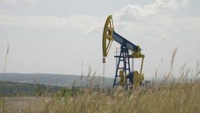 Pompa di olio che funziona nel giacimento di grano con le colline nel fondo - stock footage