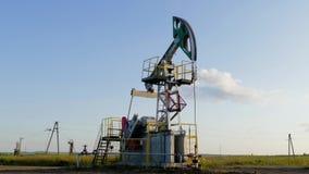 Pompa di olio funzionante sulla terra fra i campi verdi stock footage
