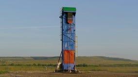 Pompa di olio funzionante sulla terra fra i campi verdi video d archivio