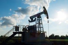 Pompa di olio funzionante sulla terra fra i campi verdi Fotografia Stock Libera da Diritti