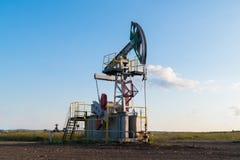 Pompa di olio funzionante sulla terra fra i campi verdi Immagini Stock