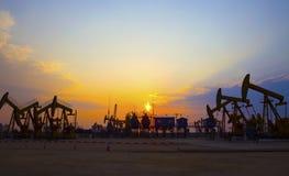 Pompa di olio sul tramonto arancio Immagine Stock