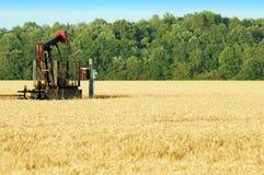 Pompa di olio in un campo di frumento Fotografia Stock Libera da Diritti