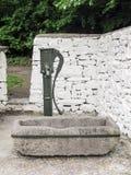 Pompa idraulica antica con la depressione di pietra dell'acqua Fotografia Stock