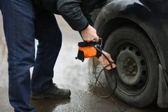 Pompaggio su dei pneumatici del veicolo Immagini Stock