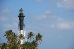 Pompano Beach Lighthouse. On the Hillsboro Mile intracoastal inlet oriented frame left surrounded by palm trees in a sunny afternoon in April with partly cloudy Royalty Free Stock Photography