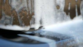 Pompas de jabón en el parachoques trasero del coche oscuro durante el lavado Cámara lenta almacen de video