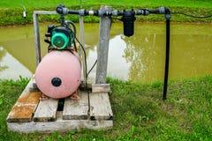 Pompe à eau électrique à l'étang pour arroser le jardin photo stock