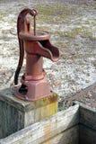 Pompe à eau manuelle antique au-dessus de vieille cuvette d'arrosage Image libre de droits