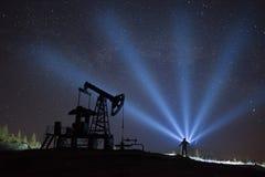 Pompe à huile et étoiles photographie stock libre de droits