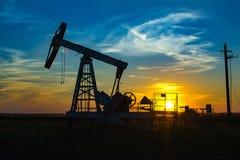 Pompe à huile sur le coucher du soleil orange photographie stock