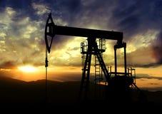 Pompe à huile sur le fond de coucher du soleil Images stock