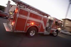 Pompe à incendie entraînant une réduction la rue images stock