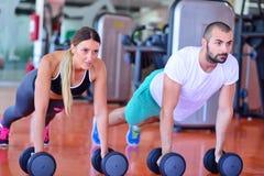 Pompe de force de pompe d'homme et de femme de gymnase avec l'haltère dans une séance d'entraînement Image stock