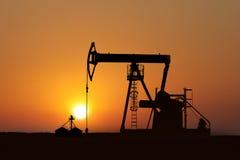 Pompe de pétrole d'isolement au coucher du soleil Photographie stock libre de droits