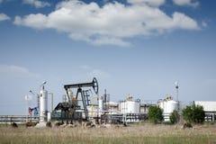Pompe de pétrole Jack et raffinerie Photographie stock libre de droits