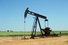 Pompe de sauterelle dans le gisement de pétrole à une ferme rurale Image libre de droits