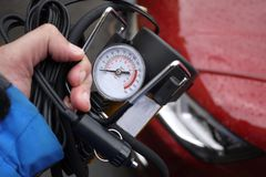 Pompe de voiture Le compresseur automatique de voiture vous aidera à pomper l'air non seulement dans les roues de votre voiture,  photographie stock