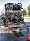 Pompe del camion di pulizia fuori lo scolo dell'acqua Immagine Stock