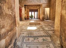 Ruins of Pompeii, ancient Roman city. Pompei, Campania. Italy. Pompei, Italy - August 9, 2017. Mosaics at entrance of archaeological remains of Domus di Paquio Royalty Free Stock Photos
