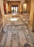 Ruins of Pompeii, ancient Roman city. Pompei, Campania. Italy. Pompei, Italy - August 9, 2017. Mosaics at entrance of archaeological remains of Domus di Paquio Royalty Free Stock Images
