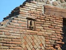 Pompei, Italy,Wall Street at Pompeii. Pompei, Italy - February 25, 2012 - Wall Street at Pompeii with a bas-relief stock images