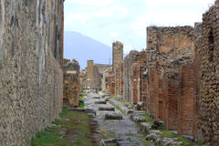 Roman Street - Pompeii. The rests of a Pompeian roman street and the city of Pompeii, which was mostly destroyed and buried under 6 m of ash and pumice in the Royalty Free Stock Photo