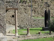 View of some Pompeii ruins. Pompeii, Italy - October 14, 2017: Ruins of Courtyards and walls in grassy fields Royalty Free Stock Photography